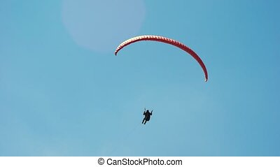 The paraglider in the sky, flies in the air streams. An extreme hobby for wealthy men. Modern equipment