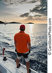 The participant of a sailing regatta is on the edge of the boat, he enjoys a victory and a sunset, he is dressing in t-shirt of orange color and cap, sailboat and island is on background