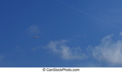 The Passenger Airplane is Flying Far in the Blue Sky above...