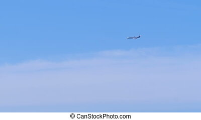 The passenger plane flies low in the blue sky