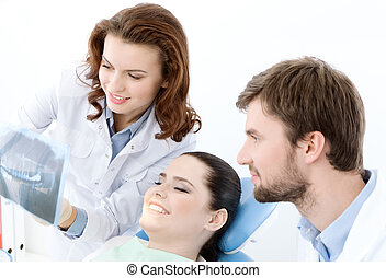 The patient examines the x ray photo of her teeth