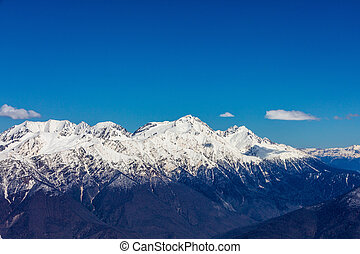 the peaks of the snowy mountains on the background of the blue sky