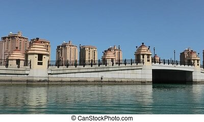 Entrance and bridge of Porto Arabia Marina at the Pearl-Qatar, Doha in Persian Gulf, Middle East from water taxi. Sunny day, blue sky. Sea view.