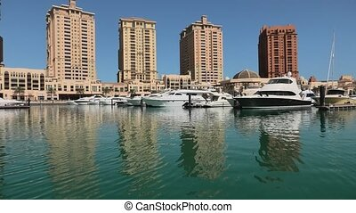 Marina corniche promenade in Porto Arabia at the Pearl-Qatar, Doha, with residential towers and luxury boats and yachts in Persian Gulf, Middle East. Sunny day, blue sky.