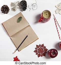 the pencil in notebook. On the table there is a cup of tea with lemon, snowflake, christmas toys and apple