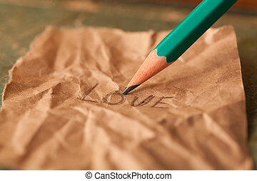 The pencil writes the word love on a paper.