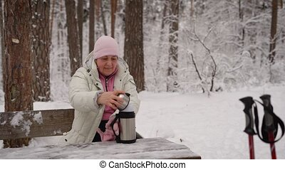 The pensioner in the winter wood. The elderly woman sits on a bench has rest and is going to have hot tea from thermos. After Scandinavian walking.