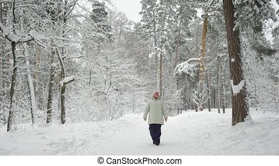 The pensioner in the wood on walk. The woman enjoys the long holiday walking  a footpath.   the snow-covered  is very useful.