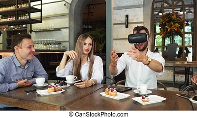 The people with virtual reality headsets on a construction site. The woman shows to group of architects and engineers the project of future interior of the room in the 3D simulator