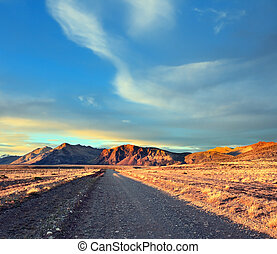 Argentine Patagonia. The gravel road between the endless pampas. The setting sun illuminates the mountains and steppe red