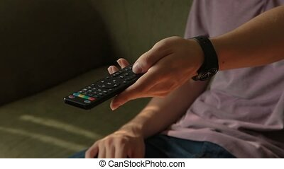 The person on a couch switches channels to remote control.