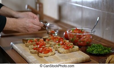 The person puts the ingredients on top of the bread for cooking bruschetta