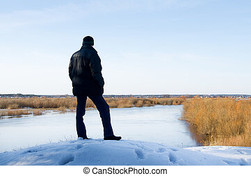 The person standing on the bank of the river