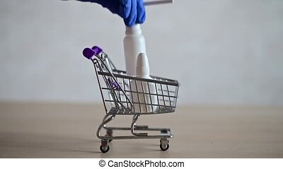 The pharmacist in the seals fills a mini shopping cart with various medicines for a viral respiratory illness. Medicine nasal spray and a tablet in the trolley. Pharmaceuticals at the pharmacy