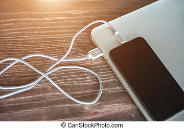 The phone is charged from a laptop. modern gadgets on the table