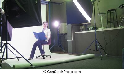 The photographer behind work: businesswoman is photographed in studio.