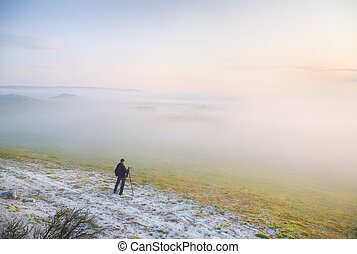 The photographer in a fog in mountains