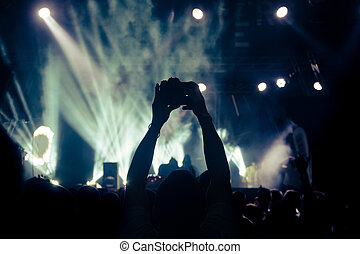 The photographer is shooting video in concert