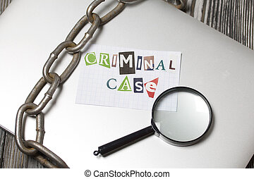 The phrase Criminal case made of letters cut from a magazine and pasted on a sheet of paper. The sheet with the inscription lies on the laptop cover. Nearby is a metal chain and a magnifying glass.