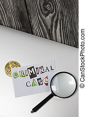 The phrase Criminal case made of letters cut from a magazine and pasted on a sheet of paper. The sheet with the inscription lies on the laptop cover. Nearby is Bitcoin and a magnifying glass.