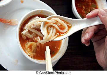Noodles in the spoon on cup of soup.