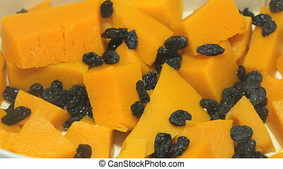 The pieces of pumpkin and raisins in a the steamer
