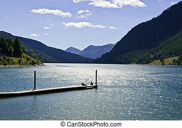 The pier - People sitting on pier above lake water at sunny ...