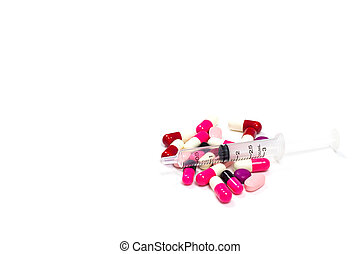 the pile of pills and capsules, a syringe with isolated