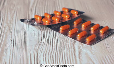 The pills in orange capsules fall on a white table