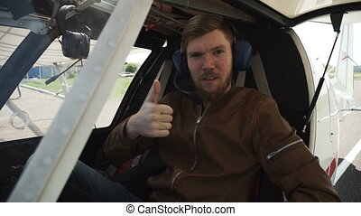 The pilot is in the cabin of a small plane. In headphones and a brown leather jacket, with a red beard.