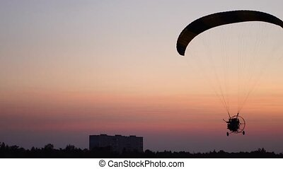 The pilot on a paraglider flies from the camera gradually moving away into the distance against the sunset beautiful sky.