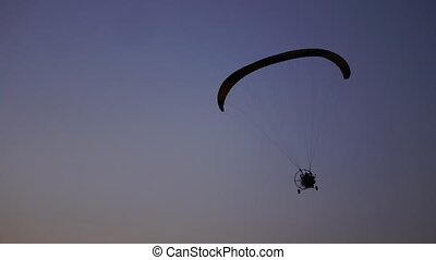 The pilot on a paraglider flies from the camera gradually...