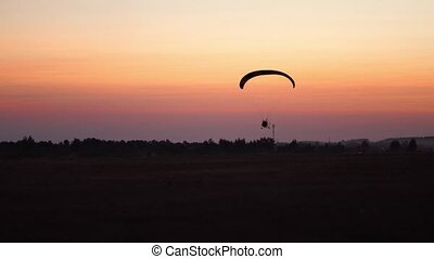 The pilot on a paraglider flies in the sky after sunset with...