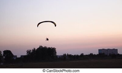 The pilot on a paraglider flies in the sky over sunset and night landscape. background