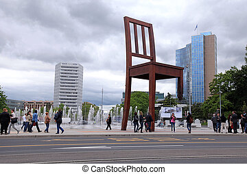 "GENEVA, SWITZERLAND - MAY, 10: The Place of Nations(Place Des Nations), fountains and gigantic ""Broken Chair"", symbol of the fight against landmines at May 10,2013 in Geneva, Switzerland. Around are the headquarters of about 250 international organizations."