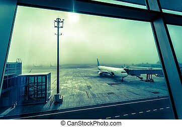 The plane at the airport in the fog