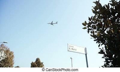 The plane flies against the inscription of the Italian street