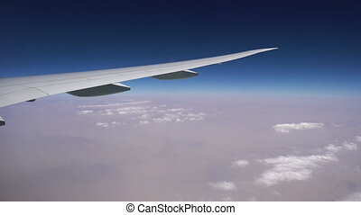 the plane flies at high altitude above the white clouds. the wing of the aircraft in the window. air flight