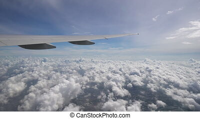 The plane flies high above the clouds and ground. The wing of aircraft in blue sky at the horizon