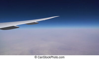 The plane flies in the stratosphere. The plane wing and the blue sky over a layer of white clouds