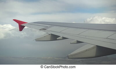 The plane flies in white clouds. View from the airplane window to the wing