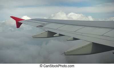 The plane flies over the city in gray clouds. View from the airplane window to the wing