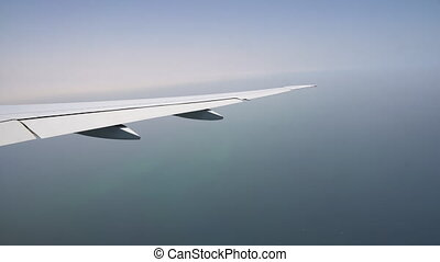 the plane flies over the sea. the wing of the aircraft in the window. boarding at the airport
