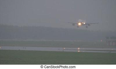 The plane landing on a rainy evening
