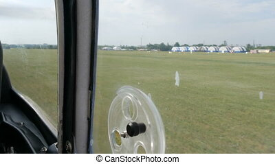 The plane picks up speed for takeoff. Small passenger plane takes off from a window on a grass field.