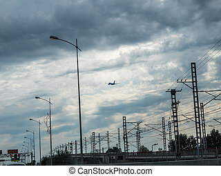 The plane takes off against the background of electric poles with wires
