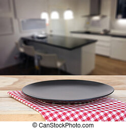 the plate on checkered tablecloth and kitchen interior blurred background