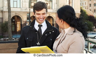 The pleasant man and woman discuss some documents and smile...