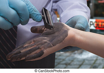 The policeman takes fingerprints from the suspect.