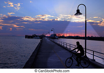 The port with the sunset and man riding a bike